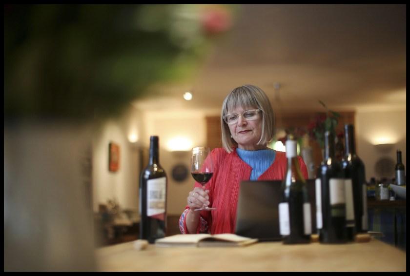 Weinkritikerin Jancis Robinson vor ihrem Laptop mit vier Weinflaschen und einem Weinglas beim Verkosten