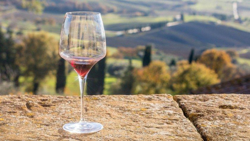 Ein fast leeres Rotweinglas steht auf einer Mauer, im Hintergrund sieht man ein Tal in der Toskana