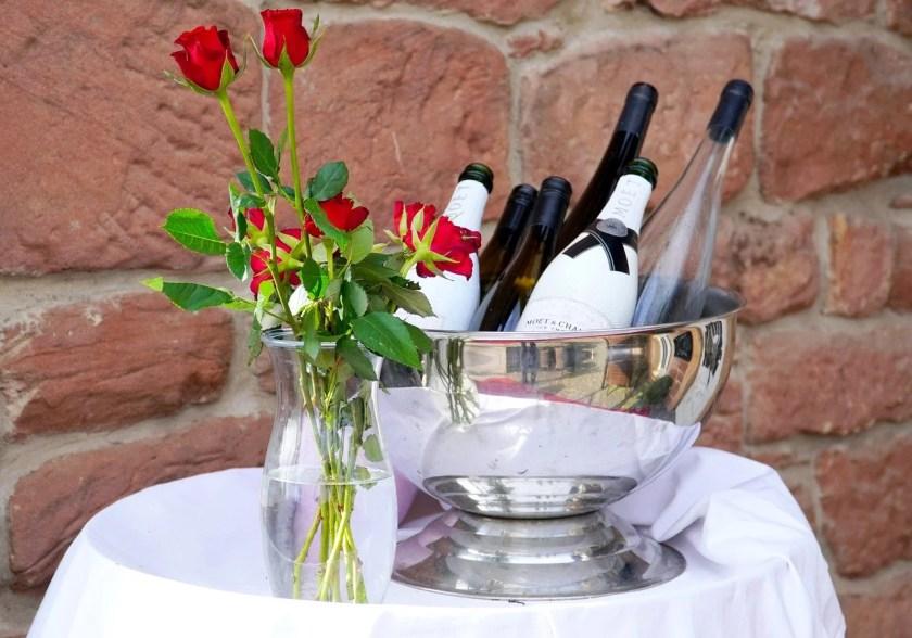 Sektkühler auf einem Tisch mit Rosen davor