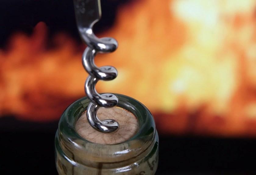 Detailaufnahme eines Korkenziehers, mit dem gerade eine Flasche Wein göffnet wird.