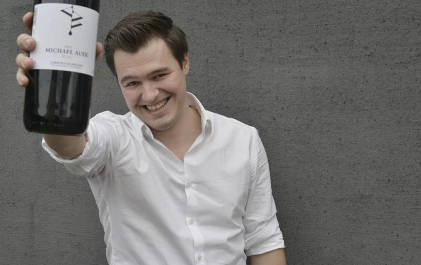 Winzer Michael Auer mit einer Flasche seines Weins in der rechten Hand