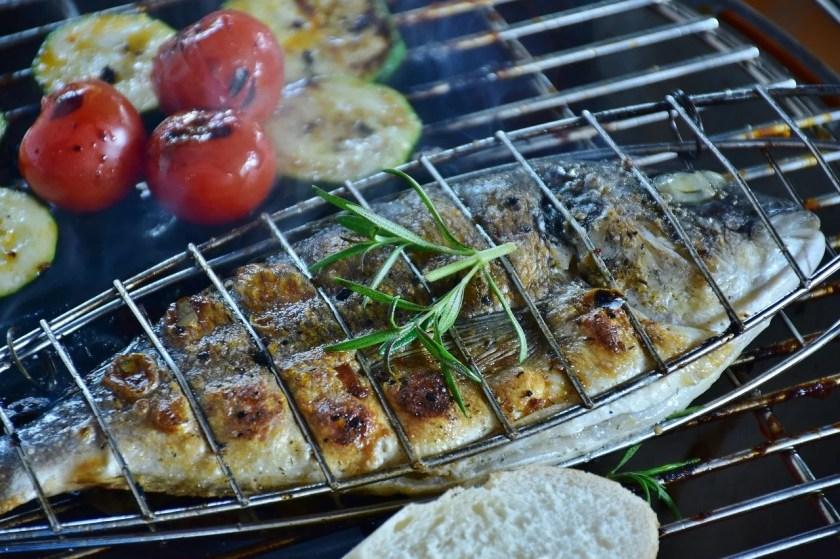 Gegrillte Dorade mit Grillgemüse auf dem Grillrost.
