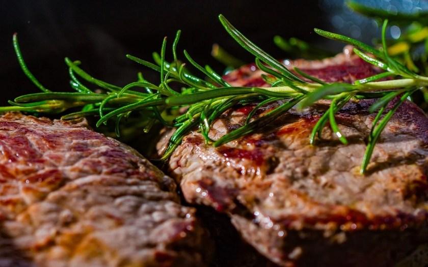 Gegrillte Steaks mit frischem Rosmarin in der Nahaufnahme.