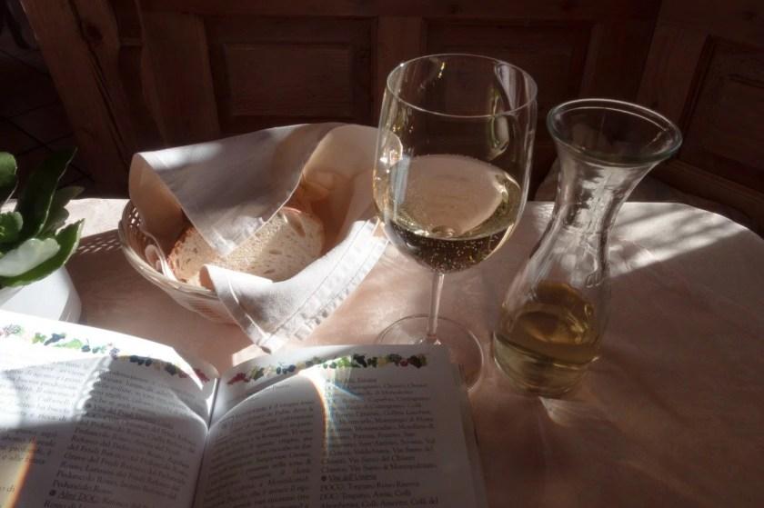 Histaminfreier Wein im Glas auf einem Tisch mit Buch und Baguette im Halbschatten
