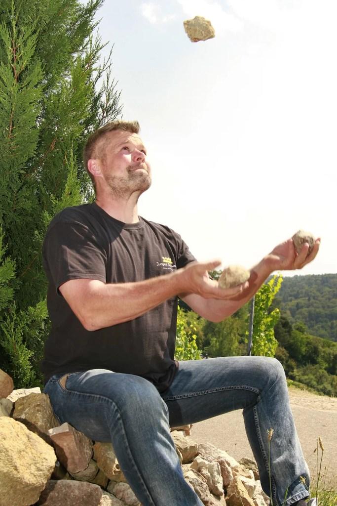 Winzer Jochen Beurer sitzt auf einer Steinmauer und jongliert mit Steinen