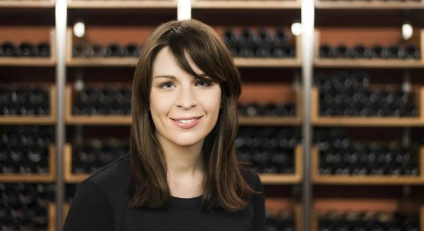 Winzerin Katharina Tinnacher vor einem Regal mit Weinflaschen