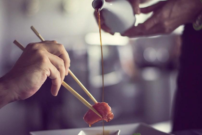 Mann hält Stäbchen mit einem Stück Lachs, über das Sojasoße gegossen wird.