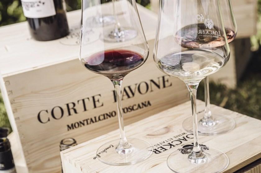 Weinkisten aus Holz von Corte Pavone, auf denen drei Gläser mit unterschiedlichen Weinen stehen.
