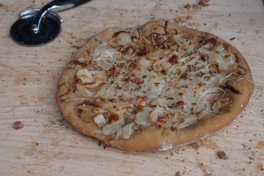 Ein runder Brotkuchen mit Zwiebeln, Speck und Kümmel auf einem großen Holzbrett, daneben ein Pizzarad