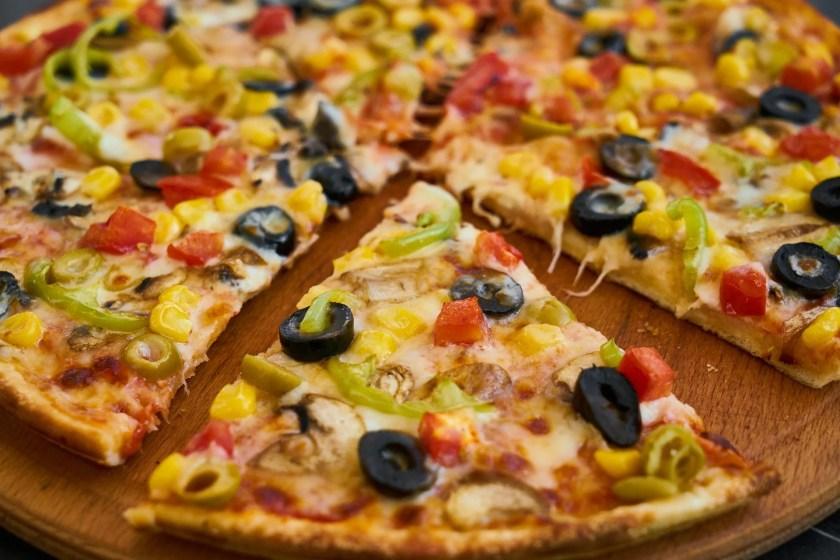 Wein zu Pizza: eine mit schwarzen Oliven belegte Pizza in der Nahaufnahme