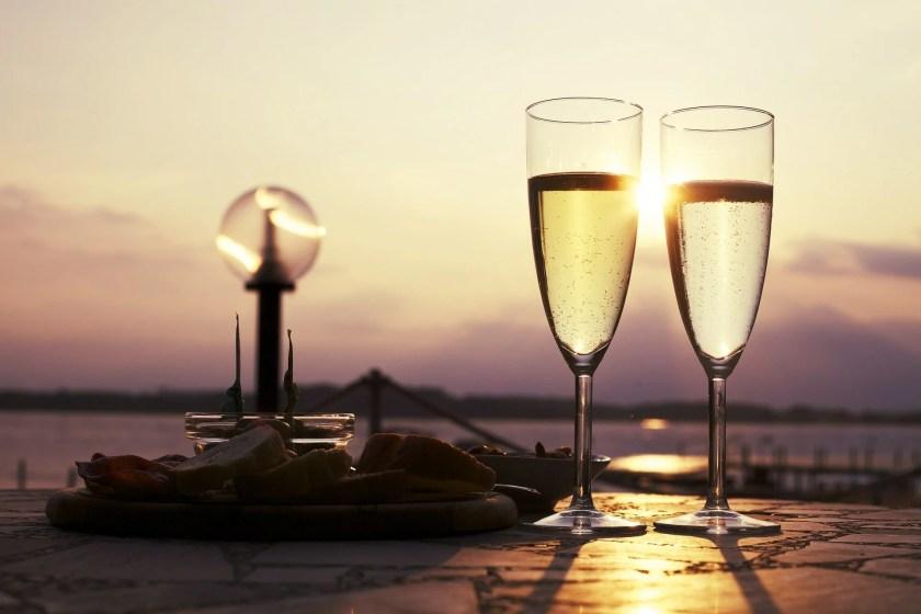 Zwei Gläser mit Schaumwein auf einem Steg bei Sonnenuntergang