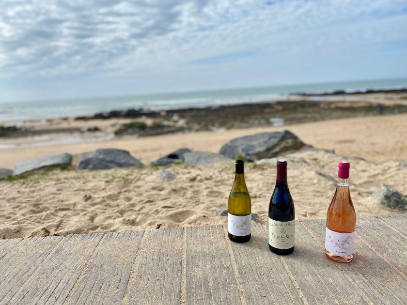 Drei Weinflaschen auf einem Holzsteg am Strand.