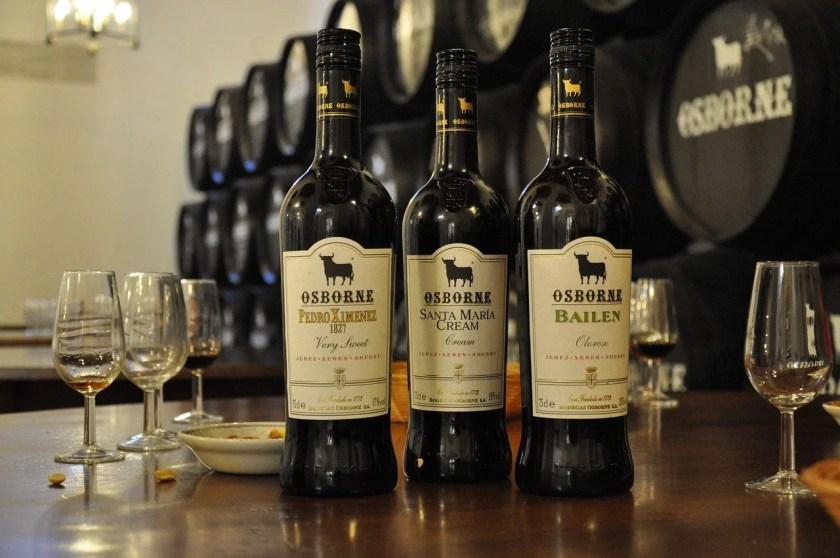 Drei unterschiedliche Sherry auf einem Tisch mit Gläsern, im Hintergrund Eichenfässer im Solera-System gestapelt