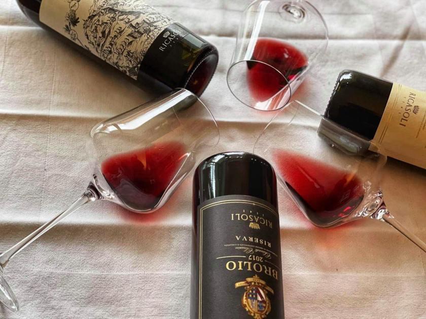 Drei Gläser mit Wein von Barone Ricasoli zusammen mit den Weinflaschen liegend auf einem Tisch