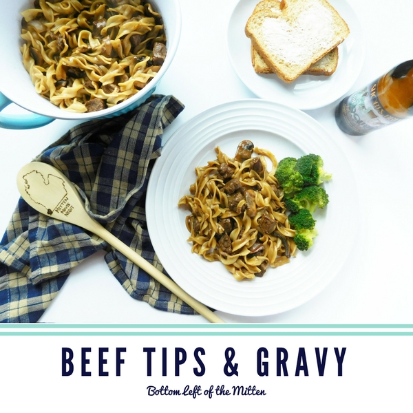 Beef Tips and Gravy in a bowl and on a plate with bread and a craft beer off to the side ready to eat.