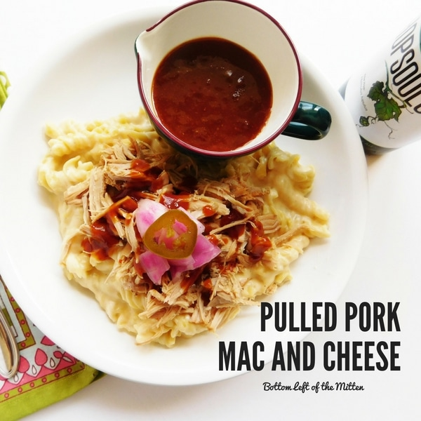 Pulled Pork Mac and Cheese on a plate with some BBQ sauce and a craft beer off to the side.