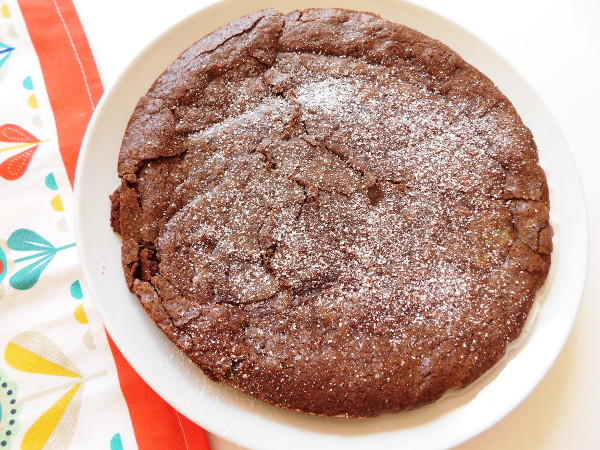 A baked Swedish Sticky Chocolate Cake on a plate ready to cut.