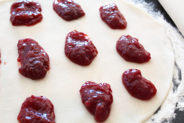 Pie crust with spoonfuls of raspberry jam sitting on it.