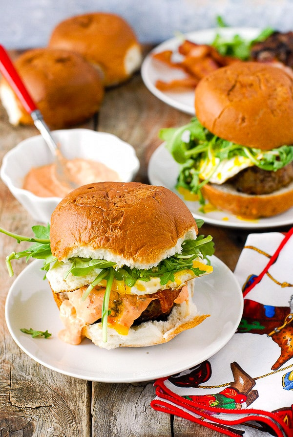 Bacon and Egg Cheese Breakfast Burgers with sriracha sour cream on a white plates