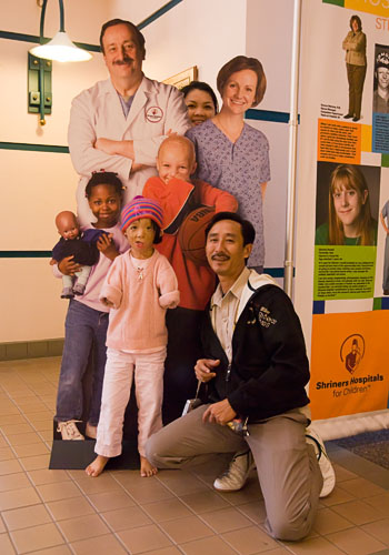 Boun Lod, Noy, and Via mugging with a cutout at the Shriners Hospital.