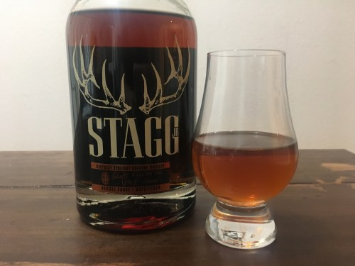 Bottle of Stagg, Jr on table with glencairn glass partially filled with bourbon