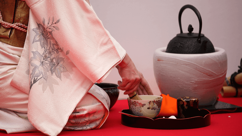 A female host prepares matcha at a traditional tea ceremony