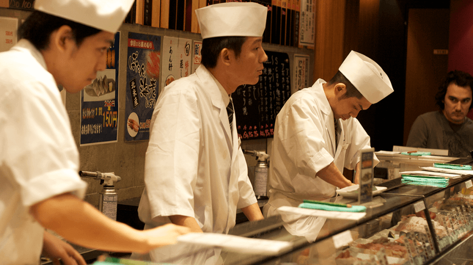 Chefs serving customers at a standing sushi bar in Shibuya, Tokyo, Japan