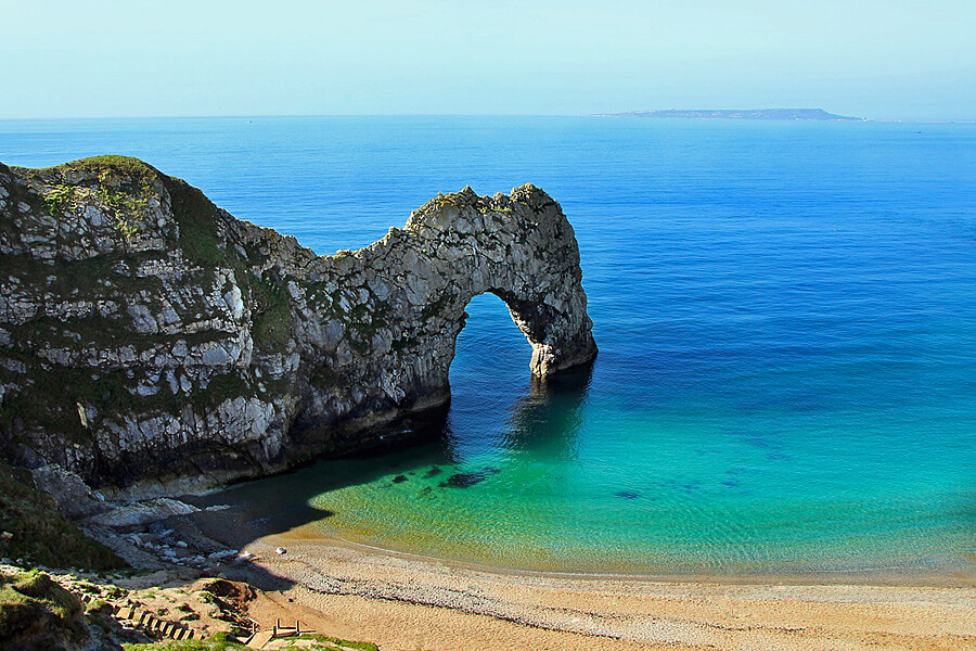The tourquise water by a sandy bay along the rugged Dorset Jurasic Coastline