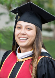 MSHRM program graduate Alyx Navarro, wearing USC graduation cap and gown and sash, looking into the camera and smiling.