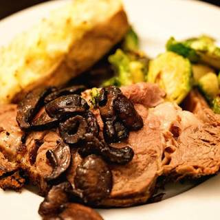 A white plate steak topped with mushrooms, twice baked potatoes and Brussels sprouts
