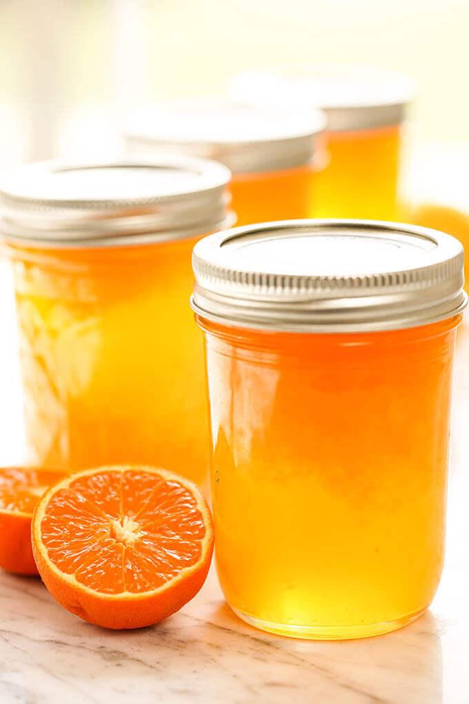 Jars of Mandarin Orange Jelly with fresh mandarins.