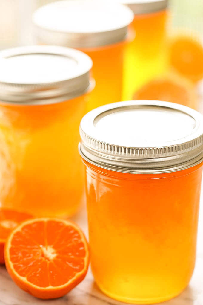 Four jars filled with mandarin orange jelly surrounded by wedges of mandarins