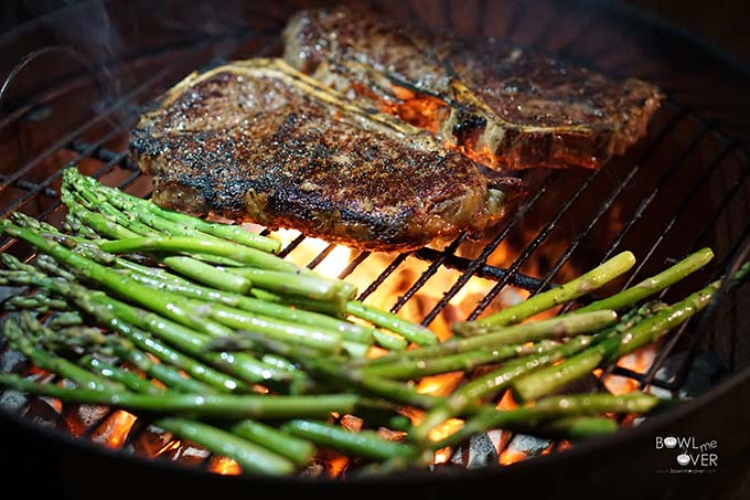 Steak on charcoal grill with asparagus.