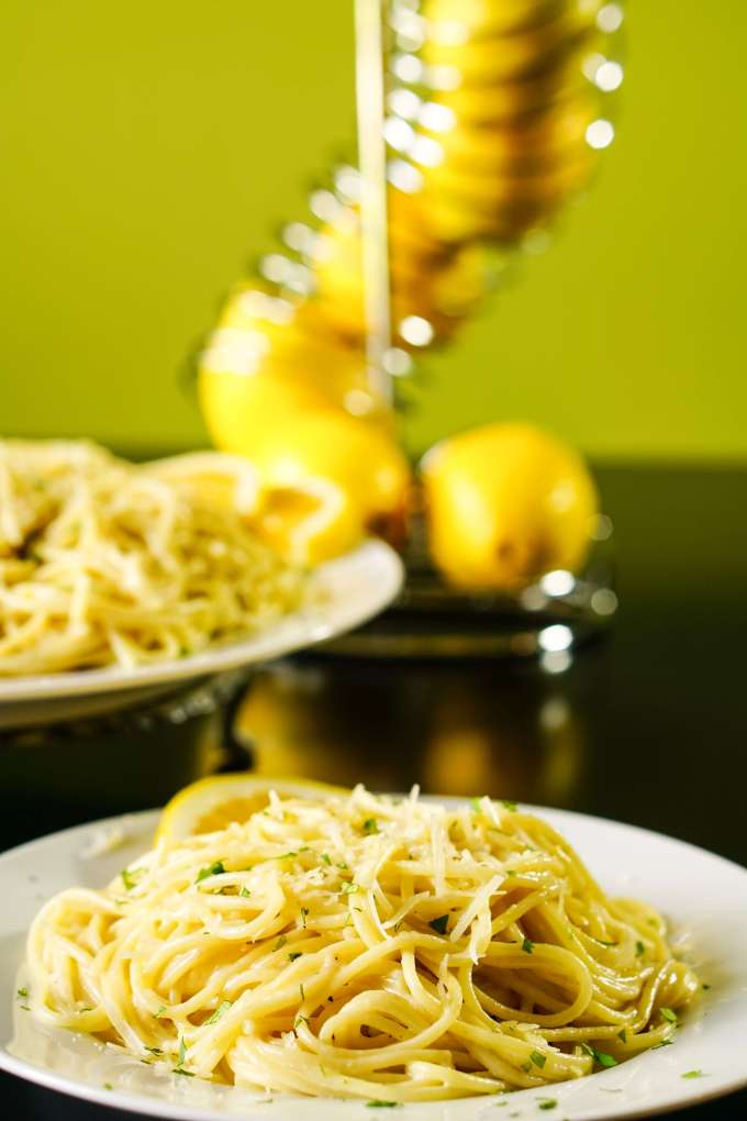 Lemon pasta on a white platter with a stack of lemons.