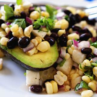 Black Bean Avocado Corn Salad piled in a halved avocado sitting on a white plate