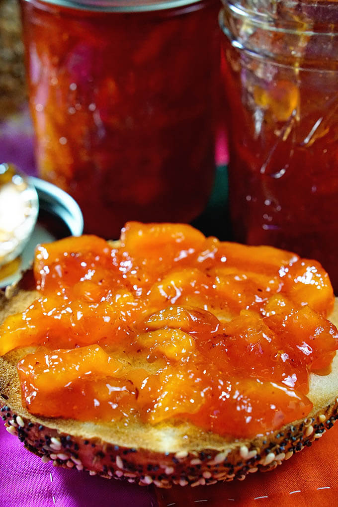 Homemade Peach Jam piled on a bagel. Peach jam recipe has step by step instructions how to make peach jam.