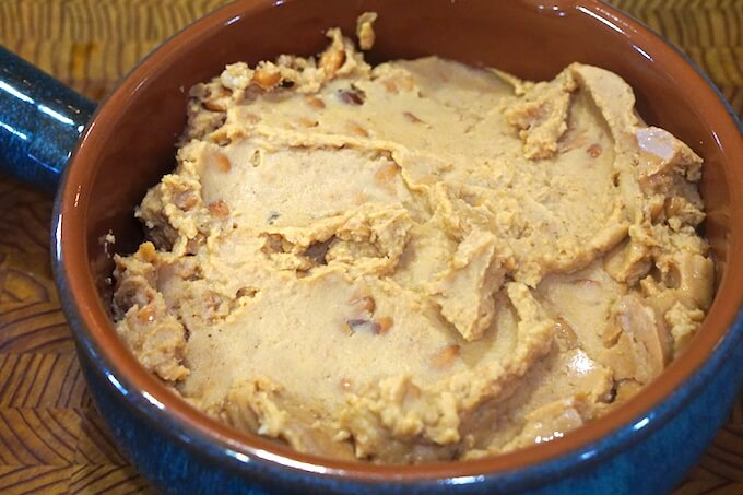Step one to make refried beans - A small casserole dish filled with refried beans.