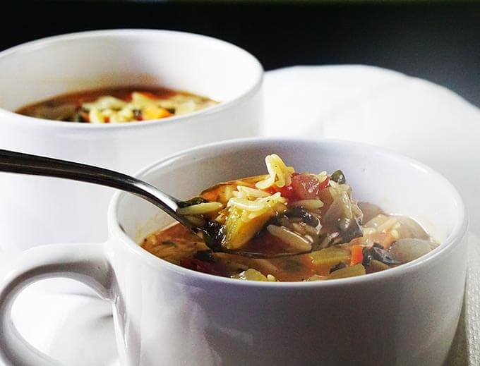 A white bowl filled with soup. There's a spoon serving up a healthy meal of vegetable orzo soup.