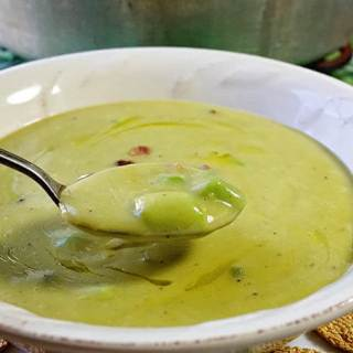 A white bowl with a spoon full of soup.