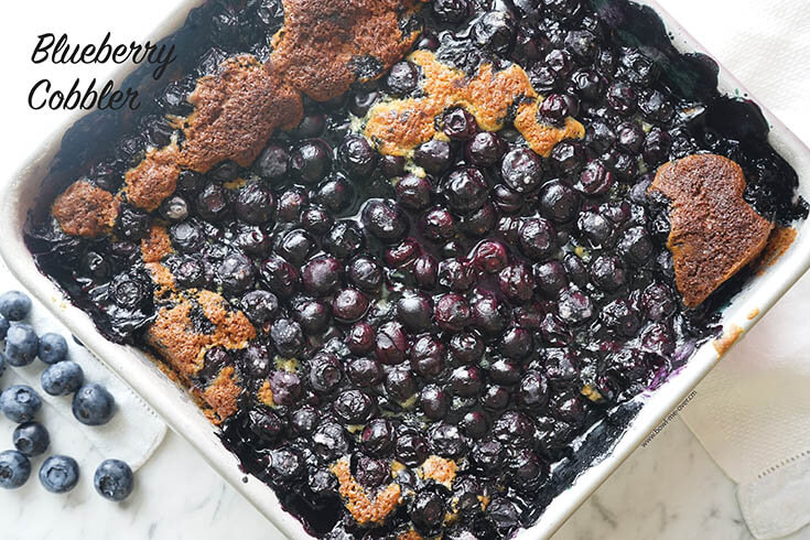 Homemade Blueberry Cobbler from scratch in white pan.