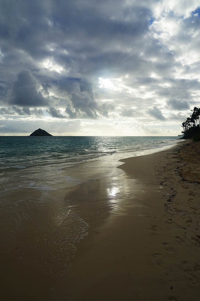 Sunrise at Lanikai Beach shows glimmering sand and sea with the sun just beginning to peak thru the clouds. The ocean waves calmly lap the shore.