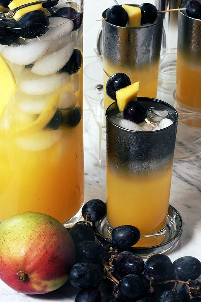 Glasses of mango punch topped with grapes and chunks of mango. The glasses are surrounded by bunches of grapes and fresh mango.