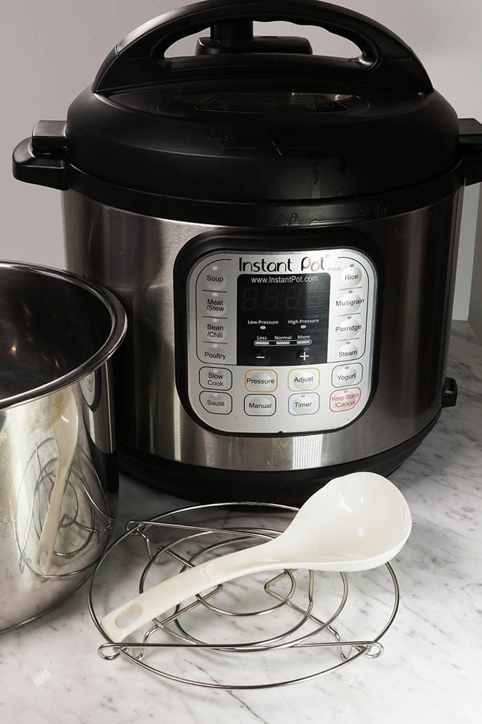 An Instant Pot Pressure Cooker equipped with a stainless steel pot, small white ladle and steaming rack.