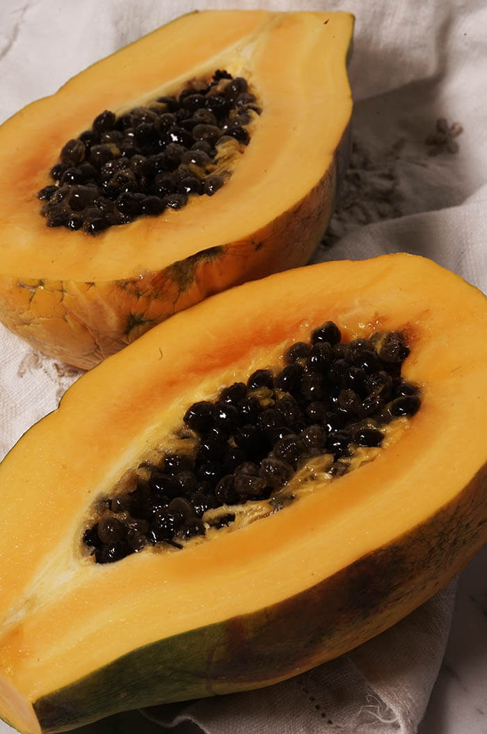 A picture of bright orange papaya sliced open showing the bright orange flesh and black seeds.