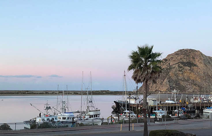 A view overlooking Morro Bay. The boats are moored waiting morning fishing trips and the huge rock is off in the distance. The blue sky is highlighted by the golden sun hitting the rock turning the background clouds purple and pink.