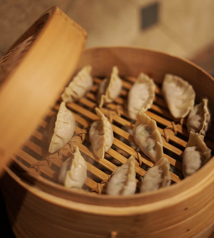 A bamboo steamer filled with pot stickers steaming on the stove