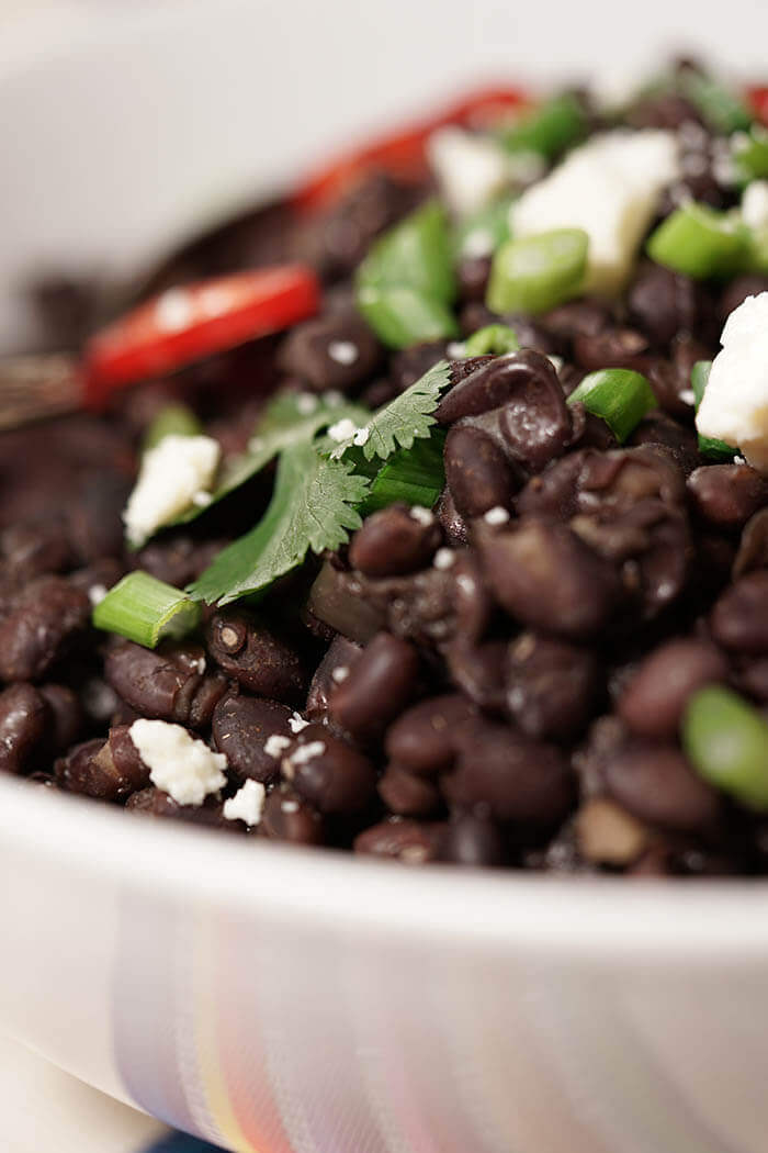 A white bowl full of cooked black beans , topped with cilantro, cojita cheese and sliced red jalapeños.