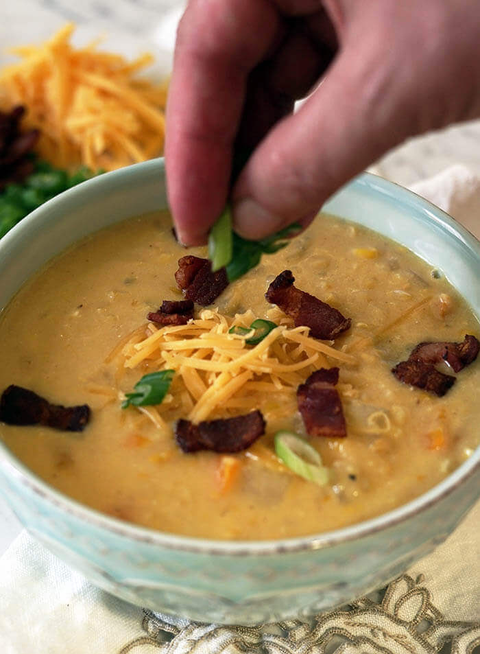 A green bowl full of corn and potato chowder topped with bacon and cheese. A hand is sprinkling thinly sliced green onions onto the top of the chowder.