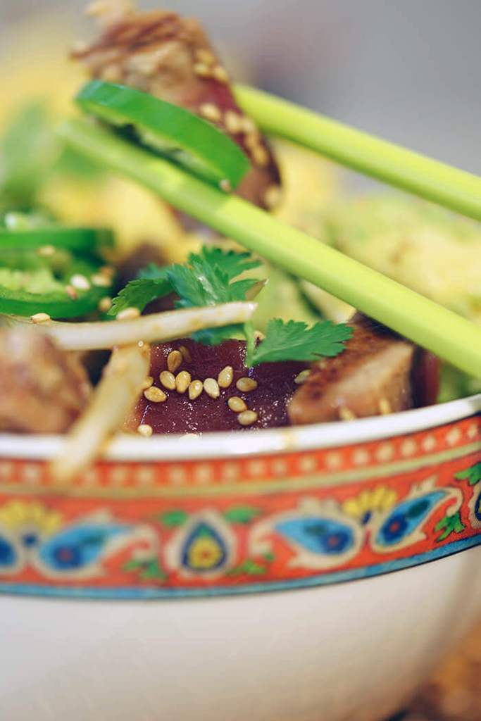 A bowl of seared tuna poke. A pair of green chopsticks grabs some tuna and is ready to take a bite!