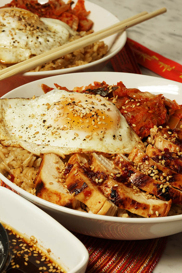 A bowl with brown rice, topped with kimchi, a fried egg and grilled chicken with a Korean BBQ Sauce Recipe. The whole bowl is sprinkled with sesame seeds.